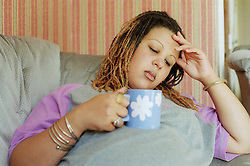 Pregnant young woman holding cup of tea looking serious,