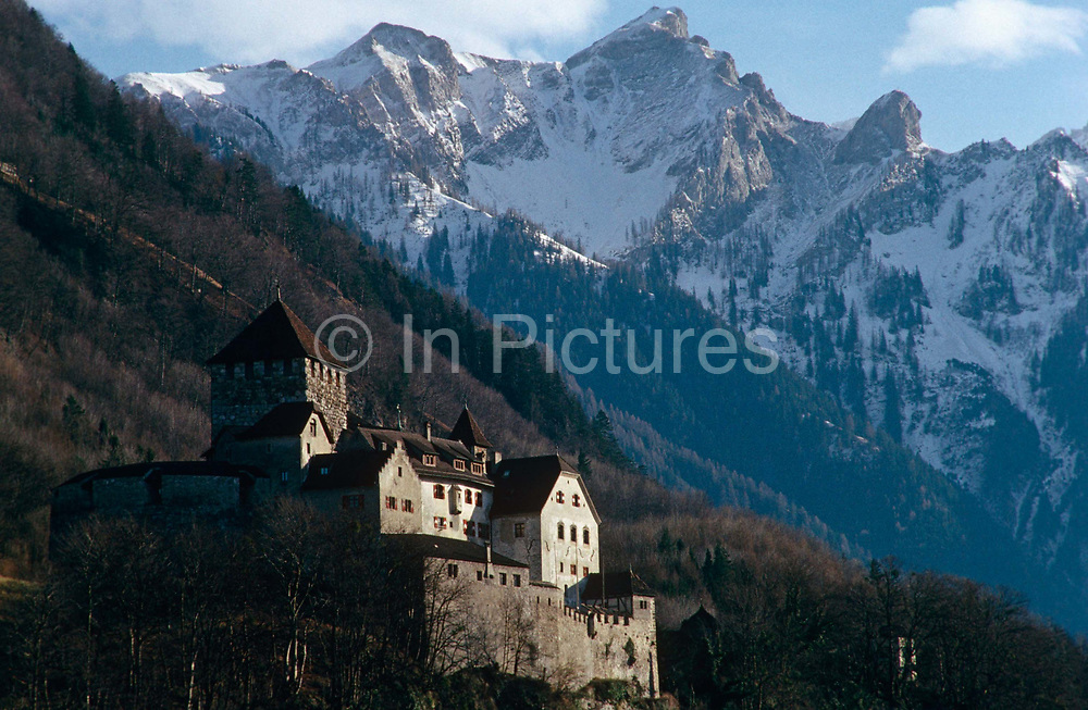 Schloss (Castle) Vaduz perches high on the slopes above Vaduz, the capital of the tiny landlocked Principality of Liechtenstein. Prince Hans-Adam II is the current resident of the Schloss. The mountain peaks in the background have snow on their jagged edges but the castle itself is free of snow and rests on the slope on a cold but fresh day. Sunlight shines on the side of the old castle walls making this a fairy tale scene of another era of history. The Liechtenstein dynasty dates a royal lineage going back to 1140 under various lines of the Hapsburgs dynasty. Liechtenstein is bordered by the Alpine countries of Austria and Switzerland and is a winter sports resort, though best known as a tax haven, attracting companies worldwide to register their assets in secrecy.