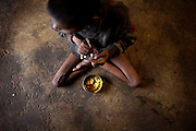 Aadite, 9, a boy suffering from a severe neurological disorder and malnutrition, is eating a curry of potatoes while sitting on the floor of his home in Kabit Pura, near the abandoned Union Carbide (now DOW Chemical) industrial complex in Bhopal, Madhya Pradeh, central India, site of the infamous 1984 gas tragedy. The poisonous cloud that enveloped Bhopal left everlasting consequences that today continue to consume people's lives. Aadite's father, Raju, a 1984 gas survivor, died in March 2013 at the age of 32, due to lungs failure. Aadite now lives in a small room with his mother, Lakshmi, 29, who works six days a week as a cleaner, his two sisters Mayuri, 12, Mahag, 7, and his younger brother Anuj, 5. None of the siblings in this family is attending school or any kind of practical education.