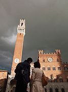 Tourists admire the Torre del Mangia tower of the Palazzo Pubblico, on Piazza del Campo, in Siena, Tuscany, Italy