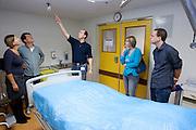 Bezoekers krijgen uitleg over de isolatieruimte van het calamiteitenhospitaal, waar patiënten met besmettelijke ziekten behandeld worden. Ter gelegenheid van haar tienjarig bestaan houdt het UMC Utrecht op 9 oktober een open dag. Bezoekers kunnen een kijkje nemen achter de schermen en ook het calamiteitenhospitaal bezoeken.<br /> <br /> Visitors are listening during a tour at the trauma and emergency hospital. The UMC Utrecht is celebrating its 10th anniversary by giving an open house to the public.