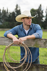 hot cowboy leaning against a wooden fence holding a lasso in his hand
