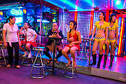 "19 JANUARY 2013 - BANGKOK, THAILAND:  Sex workers in front of a bar on Soi Cowboy in Bangkok. Prostitution in Thailand is technically illegal, although in practice it is tolerated and partly regulated. Prostitution is practiced openly throughout the country. The number of prostitutes is difficult to determine, estimates vary widely. Since the Vietnam War, Thailand has gained international notoriety among travelers from many countries as a sex tourism destination. One estimate published in 2003 placed the trade at US$ 4.3 billion per year or about three percent of the Thai economy. It has been suggested that at least 10% of tourist dollars may be spent on the sex trade. According to a 2001 report by the World Health Organisation: ""There are between 150,000 and 200,000 sex workers (in Thailand).""       PHOTO BY JACK KURTZ"