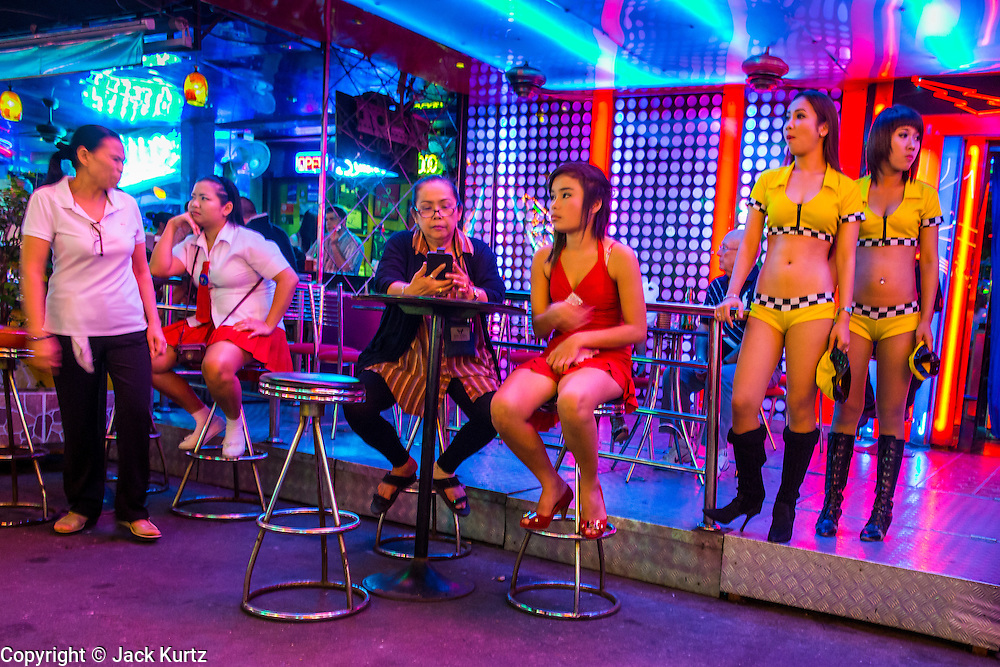 """19 JANUARY 2013 - BANGKOK, THAILAND:  Sex workers in front of a bar on Soi Cowboy in Bangkok. Prostitution in Thailand is technically illegal, although in practice it is tolerated and partly regulated. Prostitution is practiced openly throughout the country. The number of prostitutes is difficult to determine, estimates vary widely. Since the Vietnam War, Thailand has gained international notoriety among travelers from many countries as a sex tourism destination. One estimate published in 2003 placed the trade at US$ 4.3 billion per year or about three percent of the Thai economy. It has been suggested that at least 10% of tourist dollars may be spent on the sex trade. According to a 2001 report by the World Health Organisation: """"There are between 150,000 and 200,000 sex workers (in Thailand).""""       PHOTO BY JACK KURTZ"""