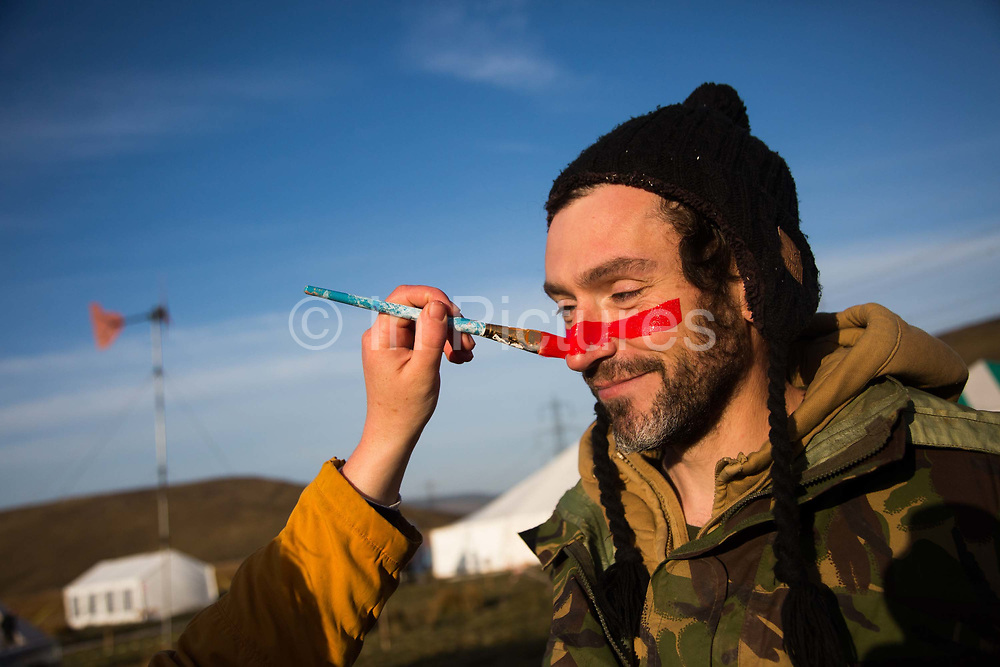 Hundreds of environmental activists stopping the open cast coal mine Ffos-y-Fran near Merthyr Tydfil, Wales from operating May 3rd 2016. An activist gets his red line painted across his face ahead of the action. The activists from Reclaim the Power wants the mine shut down and a moratorium on all future open coal mining in Wales. Open coal mining is hugely damaging to the environment and  contributing to global climate change.