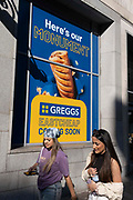 In the week that many more Londoners returned to their office workplaces after the Covid pandemic, two young women walk beneath a poster advertising a new branch of the budget bakery chain Greggs to Eastcheap in the City of London, the capitals financial district, on 8th September 2021, in London, England.