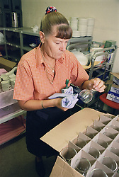 Catering assistant preparing function crockery in hospital kitchen,