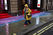 A passer-by walks alongside the rain-soaked red carpet awaiting crowds who will be seeing the English National Operas opening night of Orpheus and Eurydice at the Coliseum on St. Martins Lane, on 1st October 2019, in London, England.