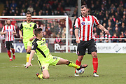 Exeter City defender Jordan Storey (38) makes a tackle on Lincoln City forward Matt Rhead (9) during the EFL Sky Bet League 2 match between Lincoln City and Exeter City at Sincil Bank, Lincoln, United Kingdom on 30 March 2018. Picture by Mick Atkins.