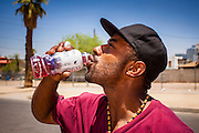 """20 JUNE 2012, PHOENIX, AZ:   A homeless man drinks vitamin water provided by """"I Will Listen"""" in Phoenix, AZ, Wednesday. June 20 is the first day of summer in the northern hemisphere. The high temperature in Phoenix Wednesday soared to over 110 (F), well above the normal of 105. The hot weather is especially stressful on the homeless, who don't have the opportunity to get into air conditioning or access to cold water. """"I Will Listen,"""" an outreach organization that assists the homeless and community of street people in Phoenix, AZ, provides free food and cold drinks to the homeless in central Phoenix. They ran out of drinks and food in about one hour during Wednesday's outreach.       PHOTO BY JACK KURTZ"""