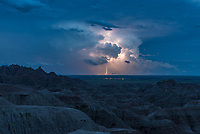 A supercell lurked in the darkness. Every few seconds a flash would illuminate the thundercloud and show a silhouette of the sharp spires of the Badlands. This was the 4th storm I watched this evening. Rumbles of thunder slowly grew louder as yet another storm approached from the west and threatened to block the view of this one. Badlands National Park is one of my favorite places to capture storms. Even when they're 100 miles away, the views here are excellent. And distant storms are preferred when I'm camping. The Badlands are very exposed to the elements. There is no escaping the rain, wind, and mud. An earlier downpour soaked me to the skin but the wind that followed dried me in minutes. The mud is the type that cakes to the bottom of your shoes making every footstep heavier. But a few hours in the hot sun and the mud is baked dry. At the time of this picture tennis-ball sized hail was reported in the Pine Ridge Reservation to the south. The lights are from the metropolis of Interior, population 94. The lightning was mostly cloud-to-cloud; this was the only strike I captured out of 500 shots.