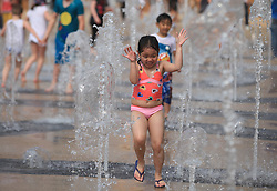 © Licensed to London News Pictures . 21/04/2014. London, UK. Children enjoy the good weather in the fountain at the Queen Elizabeth Olympic Park on Easter Monday. Photo credit: LNP