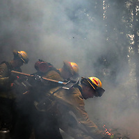 A Cal Fire. Crew is enveloped in smoke as they maintain control of a backburn along Elton Empire Road on August 26.