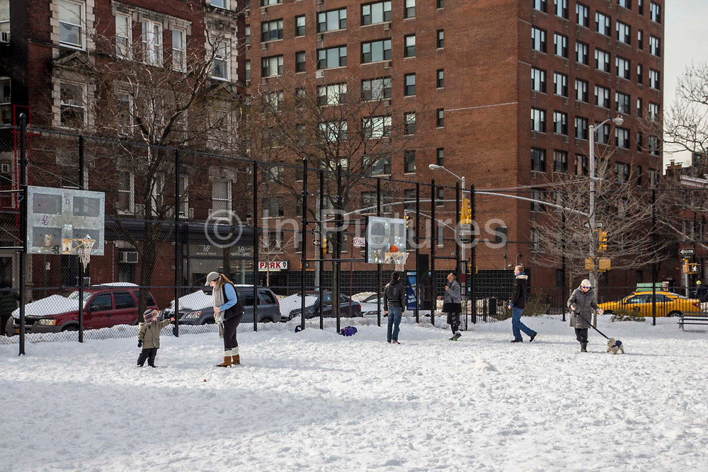 A woman plays with her young child with the snow, behind are three men playing basketball as a woman walks past with her dog just off Husdon Street, New York City,  New York, United States of America.  The whole recreation area is covered in snow after the record breaking snowstorm in January 2016.