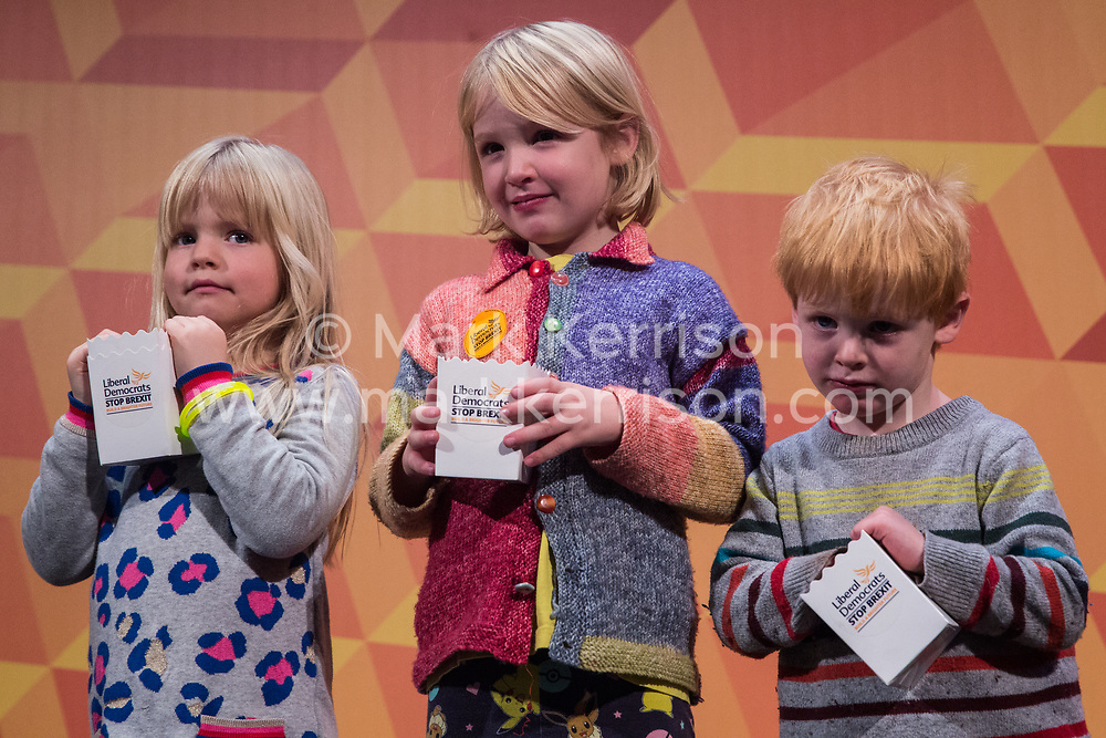 London, UK. 9 November, 2019. Liberal Democrat activists' children stand on stage at the Rally for the Future in Battersea.
