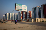 An advertising board for bank finance outisde the high rise blocks of Rajuk Uttara Apartment Project in section 16 of Uttara residential model town district on the 30th of September 2018 in Dhaka, Bangladesh. Agricultural land is slowly being taken over in the districts around Dhaka for housing development.  (photo by Andrew Aitchison / In pictures via Getty Images)