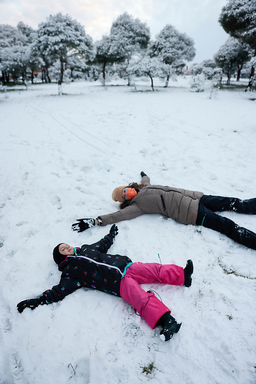 MADRID, SPAIN - JANUARY 7: A woman wearing a face mask plays on the snow with her son Lucas at a public park covered in snow as storm Filomena hits the area on January 7, 2021, in Majadahonda, Madrid, Spain.
