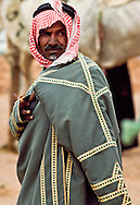 This camel trader is wearing a farrwa, a wool cloak with fleece lining.  December through March the winter can be cold. Jinayderiah, Saudi Arabia