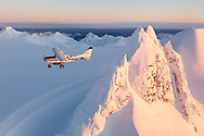 A cessna 206 flies over the glaciers, ice fields and rugged peaks of the Kenai Mountain Rage during a flightsee from Homer, Alaska.