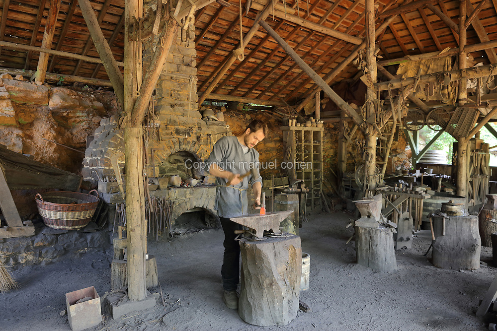 Mathieu Bonnemaison, a blacksmith, at work hammering metal on an anvil in the forge at the Chateau de Guedelon, a castle built since 1997 using only medieval materials and processes, photographed in 2017, in Treigny, Yonne, Burgundy, France. In the forge, the site's blacksmiths repair and manufacture all the metalwork needed for the project, including chisels, axes, adzes, gates and hinges. The Guedelon project was begun in 1997 by Michel Guyot, owner of the nearby Chateau de Saint-Fargeau, with architect Jacques Moulin. It is an educational and scientific project with the aim of understanding medieval building techniques and the chateau should be completed in the 2020s. Picture by Manuel Cohen