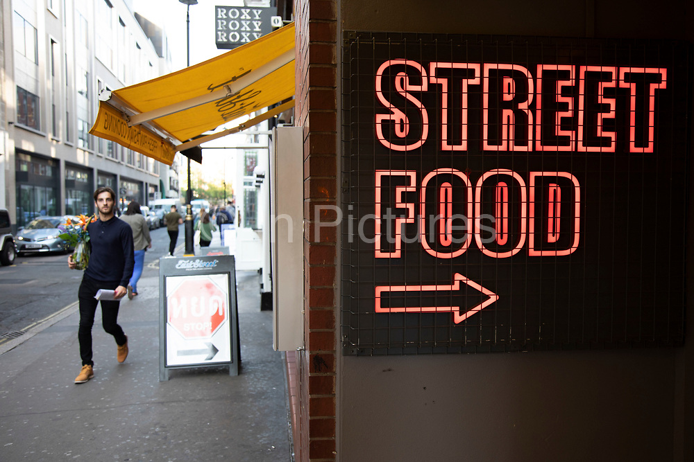 Neon sign advertising for street food in London, United Kingdom. Street food is ready-to-eat food or drink sold by a hawker, or vendor, in a street or other public place, such as at a market or fair. It is often sold from a portable food booth, food cart, or food truck and meant for immediate consumption.