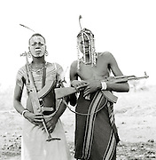 Mursi tribal men wearing face paint and head decoration with guns in Omo Valley, Southern Ethiopia.