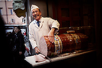 A man laughing and slicing a giant mortadella at a deli in Rome, Italy.