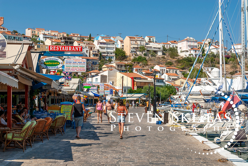 Samos. Greece.  View along the Pythagoreio waterfront which is filled with restaurants and cafes and has colourful fishing boats docked in its pretty harbour. The town of Pythagoreio is the most popular and fashionable town on the island and was named after the great philosopher Pythaogaras who was born here in 580 BC. The town is built on the ancient 6th century BC capital of the Island and is a UNESCO Cultural World Heritage Site.