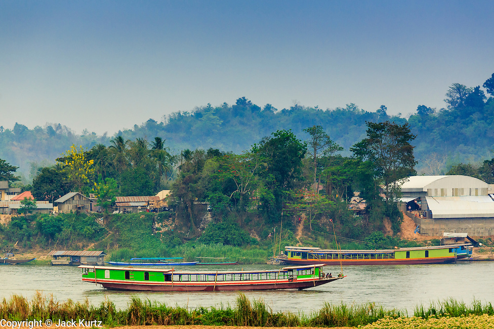 21 APRIL 2014 - CHIANG SAEN, CHIANG RAI, THAILAND: River boats on the Mekong River in Chiang Saen, Thailand. Laos is in the background. Chiang Rai province in northern Thailand is facing a drought this year. The 2014 drought has been brought on by lower than normal dry season rains. At the same time, closing dams in Yunnan province of China has caused the level of the Mekong River to drop suddenly exposing rocks and sandbars in the normally navigable Mekong River. Changes in the Mekong's levels means commercial shipping can't progress past Chiang Saen. Dozens of ships are tied up in the port area along the city's waterfront.      PHOTO BY JACK KURTZ