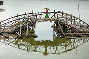 16 SEPTEMBER 2014 - SANGKHLA BURI, KANCHANABURI, THAILAND: A woman crosses the temporary bamboo bridge that is being used while the Mon Bridge is repaired. The 2800 foot long (850 meters) Saphan Mon (Mon Bridge) spans the Song Kalia River. It is reportedly second longest wooden bridge in the world. The bridge was severely damaged during heavy rainfall in July 2013 when its 230 foot middle section  (70 meters) collapsed during flooding. Officially known as Uttamanusorn Bridge, the bridge has been used by people in Sangkhla Buri (also known as Sangkhlaburi) for 20 years. The bridge was was conceived by Luang Pho Uttama, the late abbot of of Wat Wang Wiwekaram, and was built by hand by Mon refugees from Myanmar (then Burma). The wooden bridge is one of the leading tourist attractions in Kanchanaburi province. The loss of the bridge has hurt the economy of the Mon community opposite Sangkhla Buri. The repair has taken far longer than expected. Thai Prime Minister General Prayuth Chan-ocha ordered an engineer unit of the Royal Thai Army to help the local Mon population repair the bridge. Local people said they hope the bridge is repaired by the end November, which is when the tourist season starts.    PHOTO BY JACK KURTZ