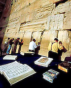 Holy scriptures are spread open on a table as men worship against the Wailing Wall at the Temple Mount in Old Jerusalem, Israel