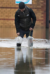 © Licensed to London News Pictures. 03/02/2021. Laleham, UK. A local resident in makeshift waders makes his way through flood water on his way to work, on a residential street in Laleham, Surrey which has flooded after the Thames broke it's banks. Large parts of the UK experience more wet conditions which is expected to bring further flooding. Photo credit: Ben Cawthra/LNP