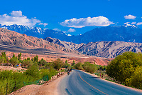 The Karakoram Highway near Tashkurgan (means Stone Fortress in Uyghur), at 10,100 feet,  It was a caravan stop on the Silk Road and all routes of the Silk Road converged here to journey southward to Pakistan. It sits on the borders of both Afghanistan and Tajikistan, and is close to the border of Kyrgyzstan and Pakistan.  The majority population in the town are ethnic Mountain Tajiks. Xinjiang Province, China.