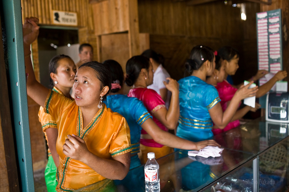 Dai women working for the Dai Minority Park after water splashing punch in time card in Yunnan, China.
