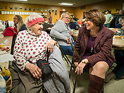 28 NOVEMBER 2019 - DES MOINES, IOWA: US Senator AMY KLOBUCHAR (D-MN), right, talks to WYLINE GARDNER, from Des Moines, at the South Des Moines Community Center. Sen Klobuchar served Thanksgiving lunches to people at the center. Sen. Klobuchar is campaigning to be the Democratic nominee for the US Presidency. Iowa holds the first selection event of the Presidential election cycle. The Iowa caucuses are Feb. 3, 2020.                 PHOTO BY JACK KURTZ