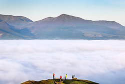 © Licensed to London News Pictures. 07/09/2021. Keswick UK. People stand at the top of Latrigg fell in Cumbria this morning and look down on the cloud inversion covering the town of Keswick in the Lake District. Photo credit: Andrew McCaren/LNP