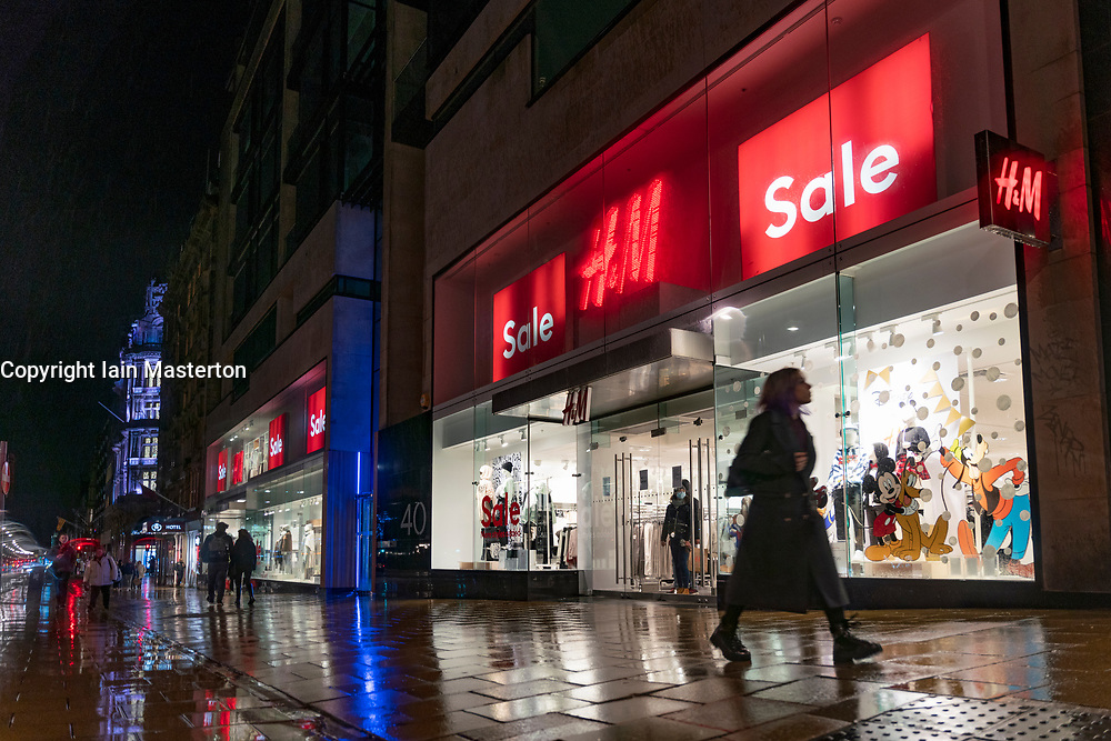 Edinburgh, Scotland, UK. 19 December 2020.  Views of streets and shops in Edinburgh City Centre on evening that Scottish Government announced the highest level 4 lockdown will be enforced from Boxing Day in Scotland.  Pic;  Members of public walks past H&M in the rain at night. Iain Masterton/Alamy Live News