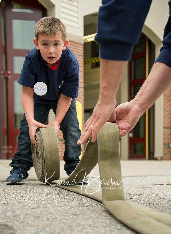 """Paul Swenson learns how to roll up the fire hose from JP Hobby during his """"day as a fireman"""" through Make A Wish on Sunday at Laconia Fire Department.  (Karen Bobotas/for the Laconia Daily Sun)"""