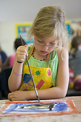 Nursery School girl painting pictures in art lesson,