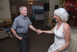 Man with disability with his wife enjoy dancing on holiday in Blackpool.