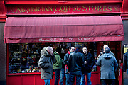Men stading drinking coffee outside The Algerian Coffee Stores Soho. On old Compton Street this shop has been in this spot for over a century. Since the doors first opened in 1887 coffee and tea have dominated the shops atmosphere. Today, 123 years later, the Algerian Coffee Stores has evolved into one of the worlds best known and leading suppliers of coffee and tea.
