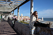 Tourists and local people enjoy the sun and the spectacular view towards the Tagus river from Sta. Luzia belvedere, on the top of Alfama district, on the way of Lisbon's nº28 yellow tram, through the central, most historic region of the city.