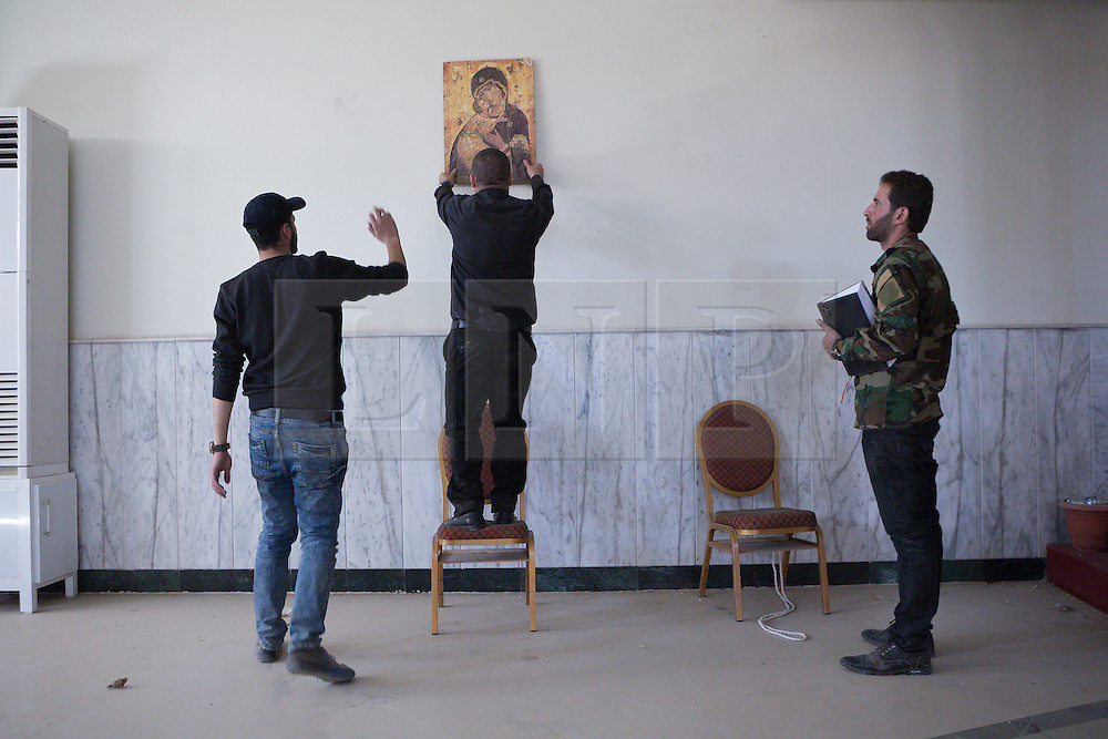 © Licensed to London News Pictures. 04/11/2016. Hamdaniyah, Iraq. Father Ignatius Offy, a Christian priest, re-hangs a picture of the Virgin Mary and Jesus Christ on the wall of a room used for events at the Christian Academy in the recently liberated town of Hamdaniyah, Iraq. Much of the academy was burnt by ISIS militants during their two year occupation of the town, but the hall was left untouched - both basketballs and footballs were found in the room suggesting that, despite the Islamic State banning sports, some extremists used the underground hall to play ballgames.<br /> <br /> Although located close to a front line, littered with improvised explosive devices and pieces of unexploded ordnance the Christian town of Hamdaniyah has only recently been cleared of ISIS extremists who stayed behind to fight. After the town's liberation as part of the Mosul Offensive residents and priests of the town are now free to take short trips to assess damage, salvage possessions and clear up the mess left by militants during their two year occupation.<br /> <br /> Hamdaniyah, and much of the Nineveh plains, were captured by the Islamic State during a large offensive on the 7th of August 2014 that saw the extremists advance to within 20km of the Iraqi Kurdish capital Erbil. Residents of the town, who included many Christian refugees who escaped there after the fall of Mosul, were then forced to seek sanctuary in the Kurdish areas. In the year and two months of the ISIS occupation churches were burnt, homes were put into use as militant accommodation and bomb factories and some buildings destroyed by coalition airstrikes. Photo credit: Matt Cetti-Roberts/LNP