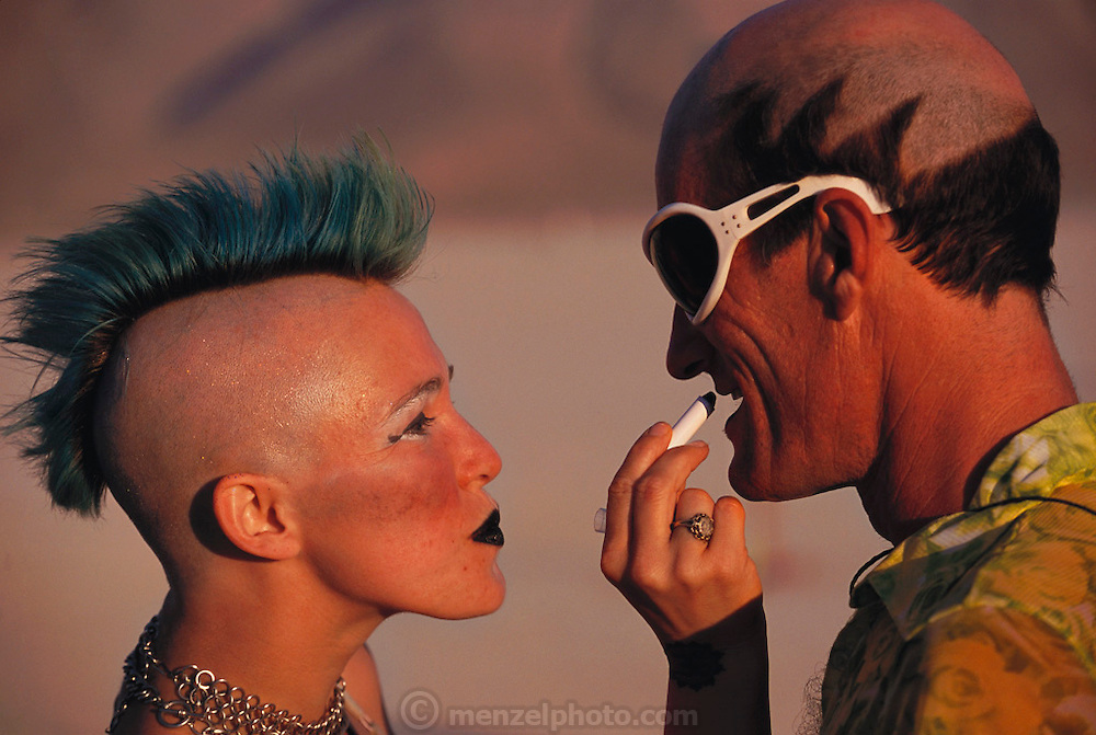 A Mohawk hair styled woman applies black lipstick to a friend at Burning Man. Burning Man is a performance art festival known for art, drugs and sex. It takes place annually in the Black Rock Desert near Gerlach, Nevada, USA.