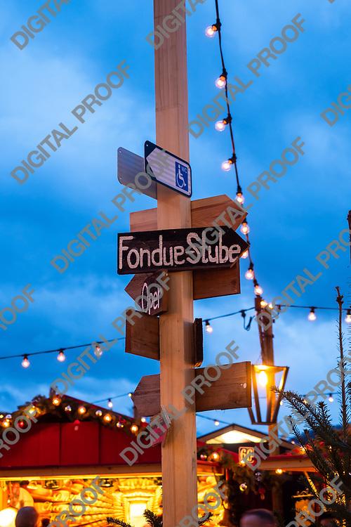 Zurich, Switzerland - December 22, 2018  Wood sign indicating the way for fondue kiosk at Christmas market held at Sechseläutenplatz
