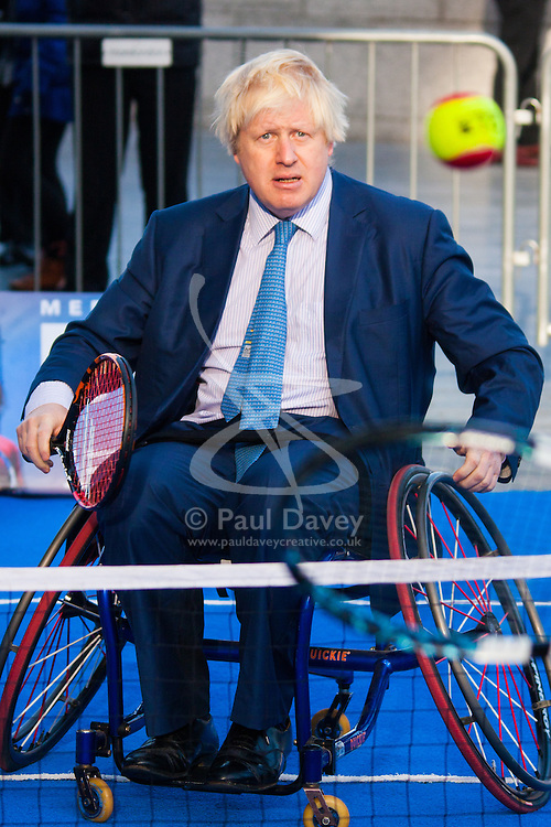 City Hall, London, November 24th 2014. Mayor Boris Johnsonwelcomes the world's best wheelchair tennis players with a game of mini tennis outside City Hall. The players are in London to compete in the NEC Wheelchair Tennis Masters 2014, being held at the Lee Valley Hockey and Tennis Centre, being held from 26 - 30 November. PICTURED: Mayor Boris Johnson keeps his eye on the ball.