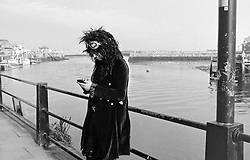 © Licensed to London News Pictures.01/11/15<br /> Whitby, UK. <br /> <br /> A man wearing gothic clothing uses his phone as hundreds of visitors attend the Whitby Goth weekend in Whitby, North Yorkshire. The event began in 1994 to celebrate goth culture and music and takes place twice each year. <br /> Thousands of extravagantly dressed people attend the popular event wearing Steampunk, Cybergoth, Romanticism, Victoriana and other clothing as they take part in the celebration of Goth culture. <br /> <br /> Note to Editors - Picture shot on Kodak Tri X 400ISO film.<br /> Photo credit : Ian Forsyth/LNP