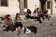 A group of American interior design students sketch buildings adjacent while sitting on steps of public building in Florence's Piazza Di Annunziata. The small class is made up mostly of young women and there is a young man who is apparently teaching one woman how to capture the finer points of the architecture opposite. They all have sketchpads on their laps and are either looking into the distance, memorising the landscapes - or using pencils to reproduce these features on to paper. Florence and other Italian cities are full of young Americans studying music and painting, art and design, completing and complimenting US-based courses often as foreign exchange students or as residential terms.