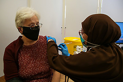 © Licensed to London News Pictures. 25/10/2021. London, UK.  Nassima Larbi, a NHS vaccinator, administers the Pfizer/BioNTech Covid-19 booster vaccine to 72 year old Janette Nicholls, at a vaccination centre in north London. Ministers are urging those eligible to get a Covid-19 vaccine and booster jab this winter amid fears of further restrictions as coronavirus infection cases rise. The Government is considering cutting the interval between booster jabs and the second dose of a Covid-19 vaccine from six to five months. Photo credit: Dinendra Haria/LNP