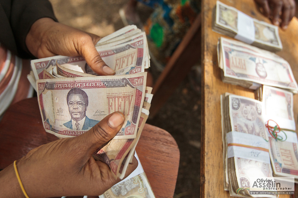 A staff member from a local bank counts money during a UNICEF-sponsored social cash transfer programme distribution in the village of Julijuah, Bomi county, Liberia on Tuesday April 3, 2012. Beneficiary households receive monthly transfers that vary according to the size of the household, with additional sums provided for each child enrolled in school. Families are selected for participation in the programme based on two key criteria: they must be both extremely poor and labour-constrained.